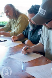 Graham Burns, Matt Hagerman, and Chris Burns sign contracts (in crayon) in a photo from the prank announcement.