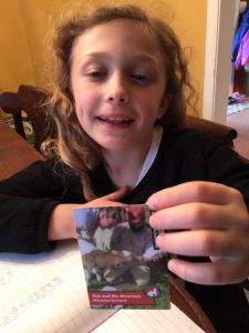 Amelia Crush, 8, of Lovettsville checks out the Moutoux Orchard trading card she got last week in school. (Courtesy of Spring House Farm)