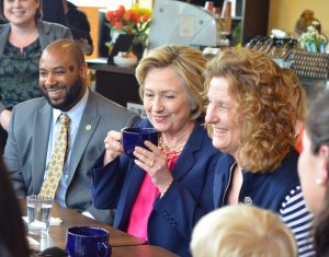 Hillary Clinton sits with Loudoun County Supervisor Koran Saines (D-Sterling) and co-owner of Mug'N Muffin Shanda Koehler on Monday. (Danielle Nadler/Loudoun Now)