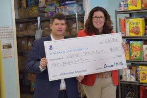 Former Loudoun Interfaith Relief volunteer presents the General Mills donation to Executive Director Jennifer Montgomery.