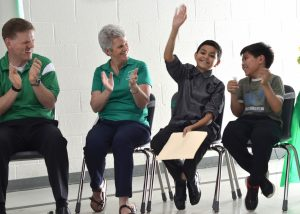 From left, former Guilford Principal David Stewart, longtime Guilford teacher Joanne Luoma, and fifth-graders Alexander Ayala and Alexander Singh greet the crowd at the school's 50th birthday celebration Thursday. (Danielle Nadler/Loudoun Now)