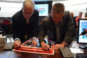 Western supervisors Geary M. Higgins (R-Catoctin) and Tony R. Buffington (R-Blue Ridge) sign a poster to commemorate the end of the Short Hill application. (Renss Greene/Loudoun Now)