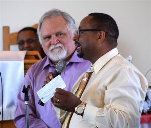 Pastor Carlos Lawson thanks members of the South Riding Rotary Club for a donation to help preserve Prosperity Baptist Church as historian Larry Roeder looks on..