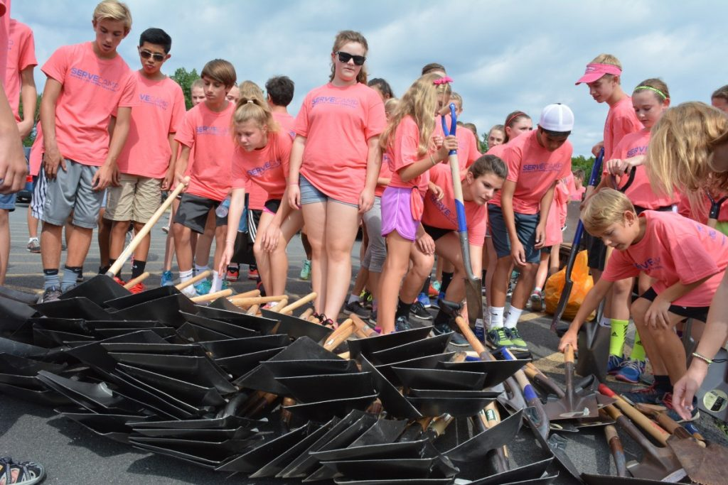 Campers pick up shovels from a pile of 120 before starting work. (Renss Greene/Loudoun Now)