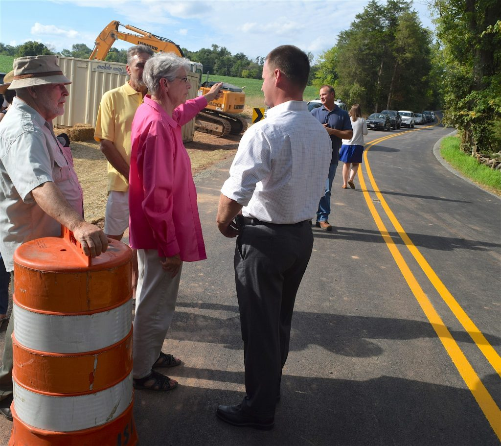 Supervisor Tony Huffington, left, talks with Aleta and James Kennedy after a ribbon-cutting ceremony for the re-opening of Fleetwood Road. The Kennedys have lived on the once quiet gravel road since 1971.