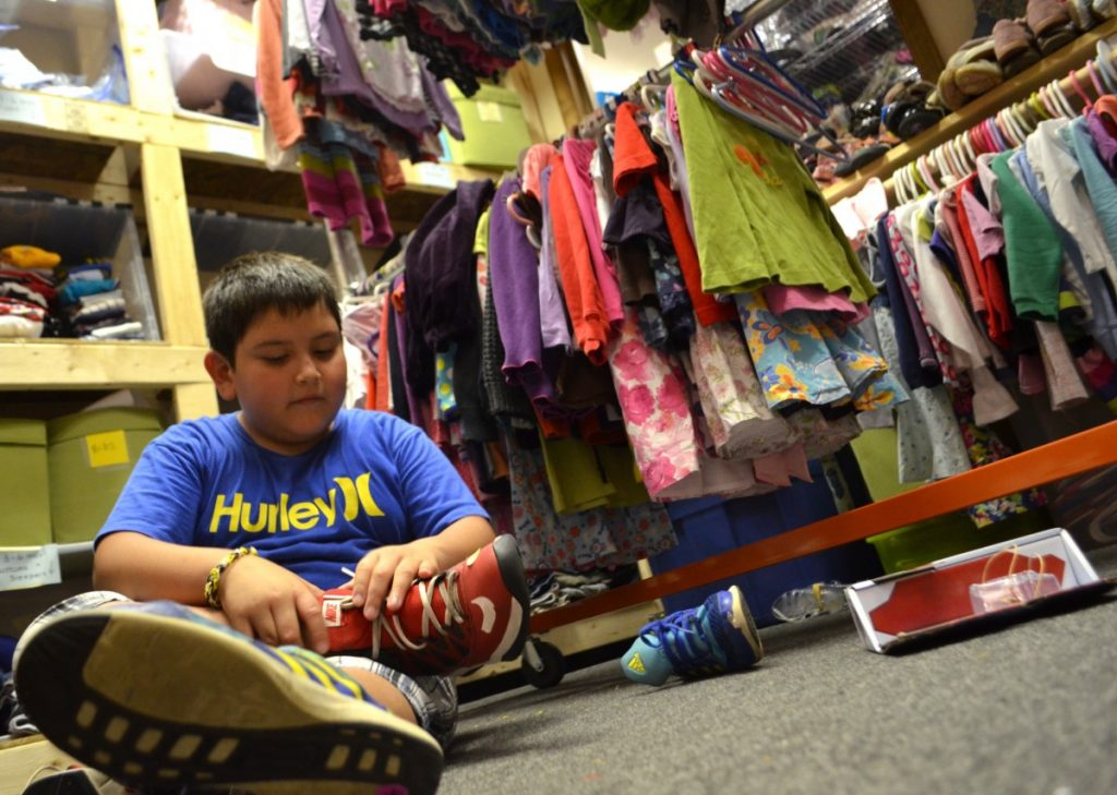 Chris, 10, tries on a pair of Nikes at Mobile Hope on Thursday. [Danielle Nadler/Loudoun Now]