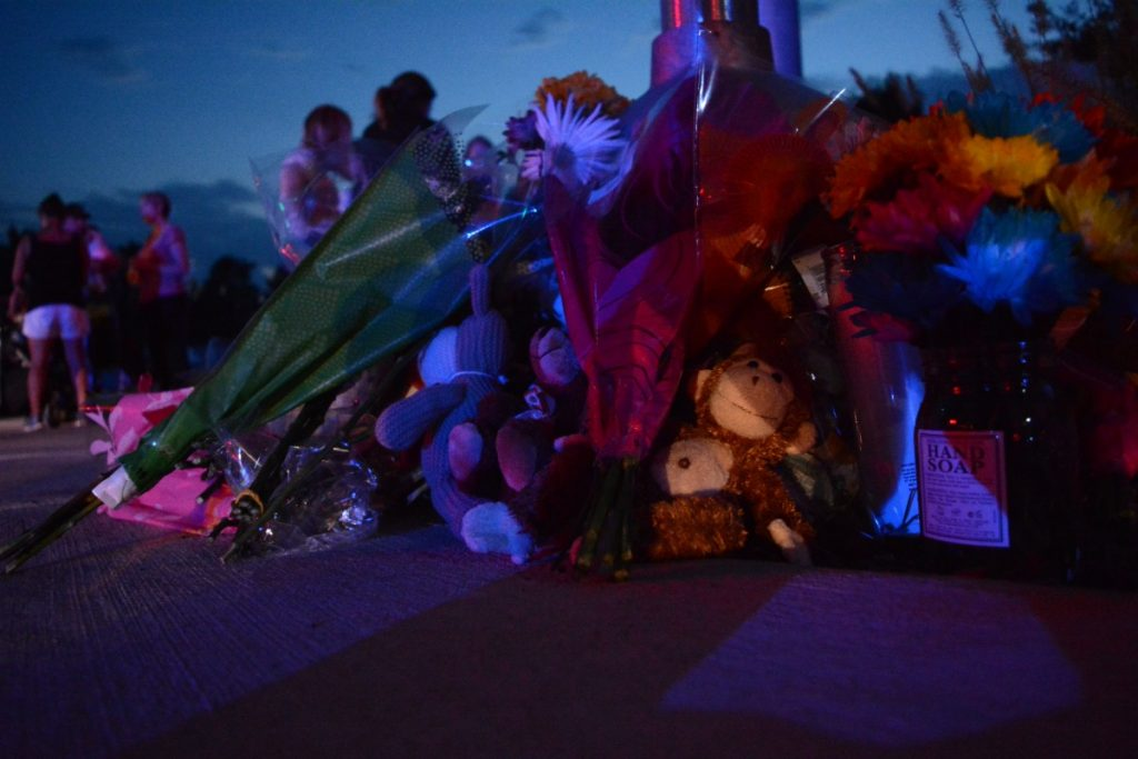 Two signal poles were piled high with flowers and toy stuff animals by the end of the vigil. (Renss Greene/Loudoun Now)
