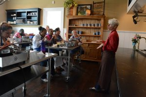 Chef Bonnie Moore teaches cafeteria employees while they try their own latest creations. [Renss Greene/Loudoun Now]