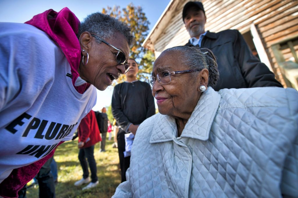 Yvonne Neal Thornton, who attended the Ashburn Colored School in 1930s and '40s, is greeted by friends and volunteers after she visited during clean up. [Douglas Graham/Loudoun Now]