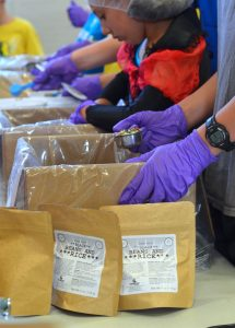Volunteers package hydrated beans and rice at Generosity Feeds. [Danielle Nadler/Loudoun Now]
