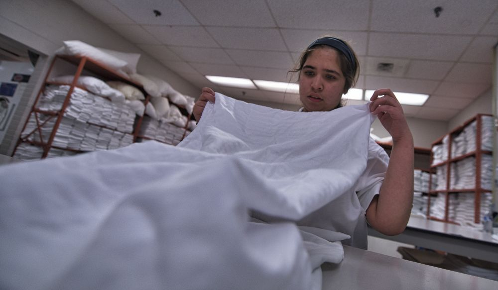 Project SEARCH intern Allyson Foster folds sheets at National Conference Center. [Douglas Graham/Loudoun Now]