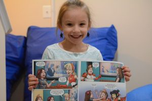 Tenley Schnur with a copy of the comic book in which she stars. (Renss Greene/Loudoun Now)