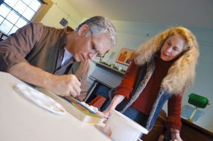 Artist and instructor Colette Kalvesmaki works with Don Phillips during her weekly iconography classes, held at Trinity House Café in downtown Leesburg. [Danielle Nadler/Loudoun Now]